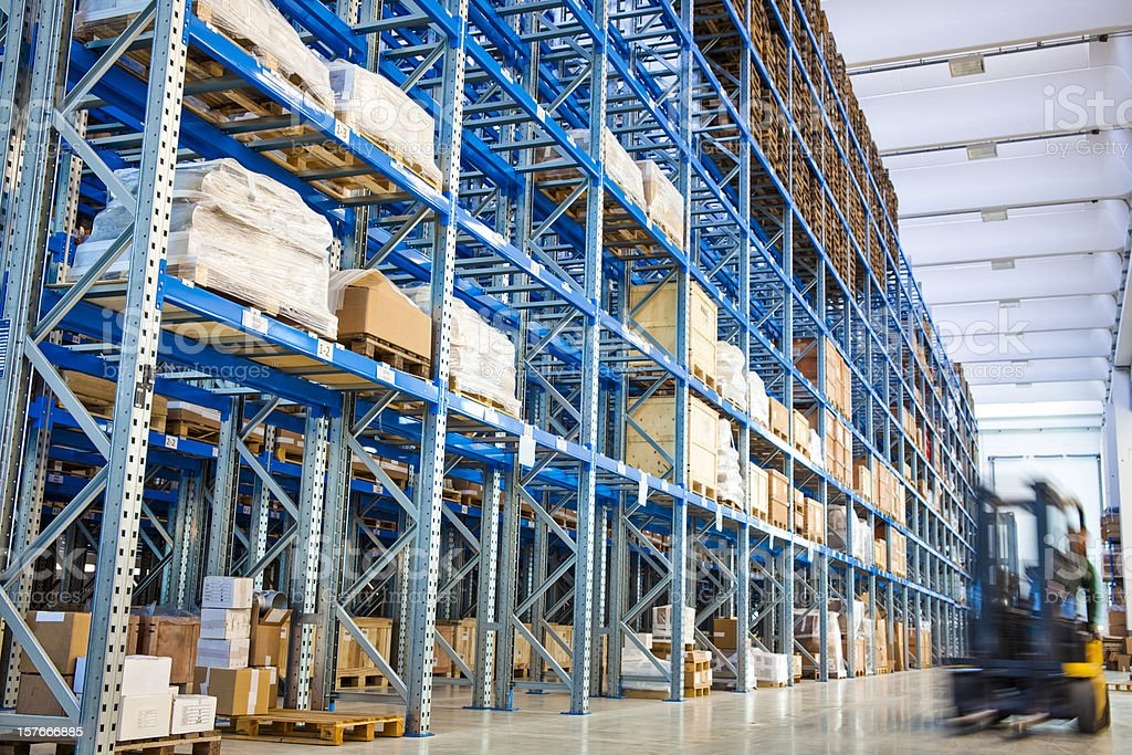 Forklift driving past blue industrial storage racks stock photo