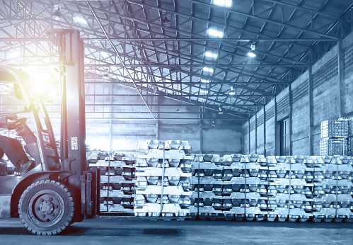 Forklift handling pack of aluminum ingot in warehouse. Distribution warehouse and industrial raw material logistics. Distribution warehouse and industrial raw material logistics.