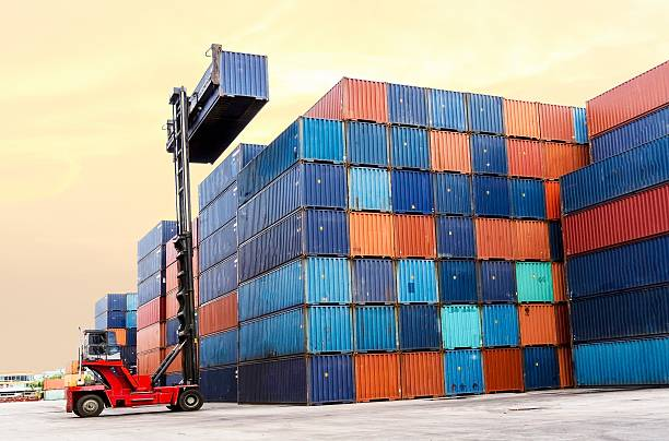 Forklift handling the container box at dockyard stock photo