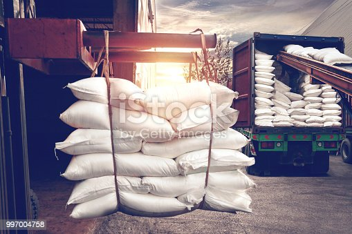 Forklift handling white sugar bags from warehouse for stuffing into container truck for export, vintage tone.