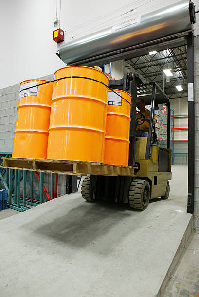 forklift in warehouse carrying yellow barrel forklift carrying industrial barrel drum container stock pictures, royalty-free photos & images