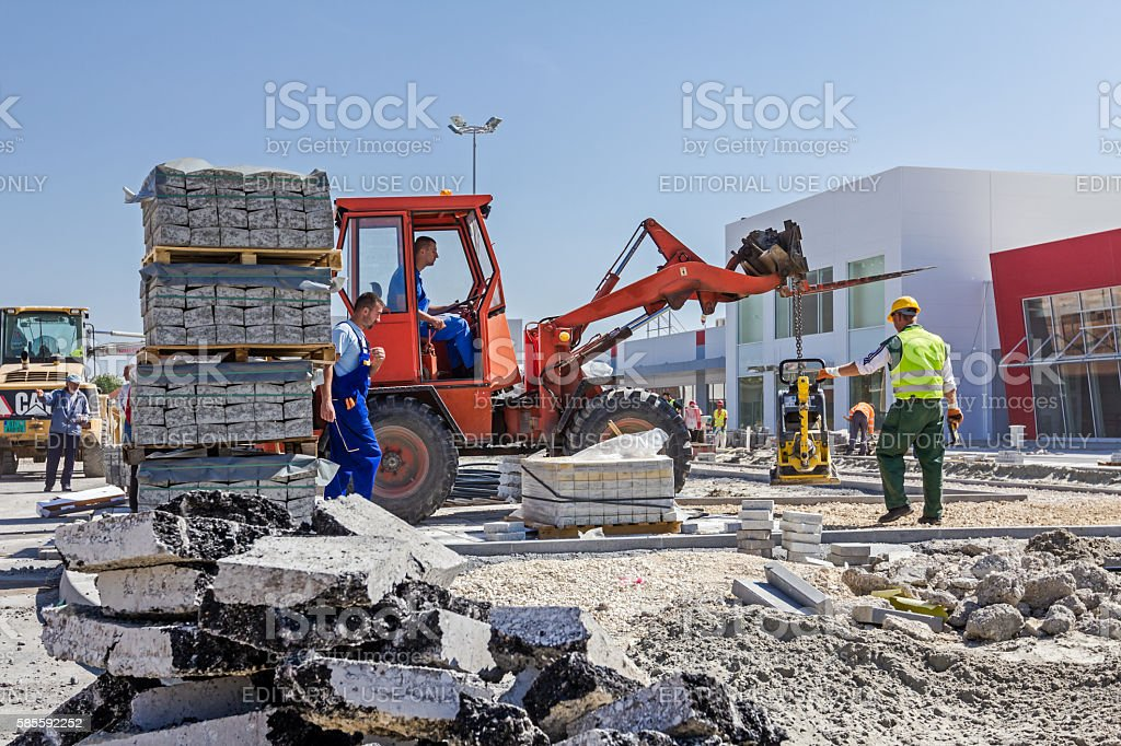 Forklift is carry vibration plate compactor machine at building stock photo