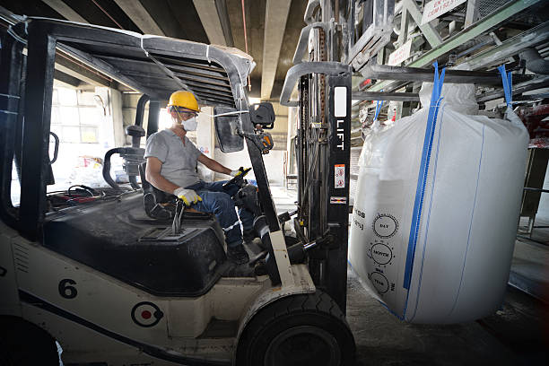 Forklift lifting huge bag of cement stock photo
