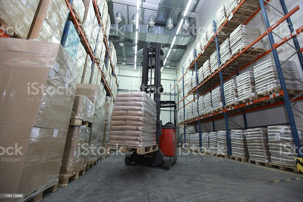 Forklift loader with pallet of sacks in distribution warehouse stock photo