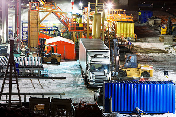 forklift loading semi truck near oil drilling tower at night - lorries unloading stock photos and pictures