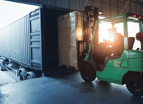 Forklift loading shipment goods pallet into container shipping truck. Cargo freight, Logistics and transportation.