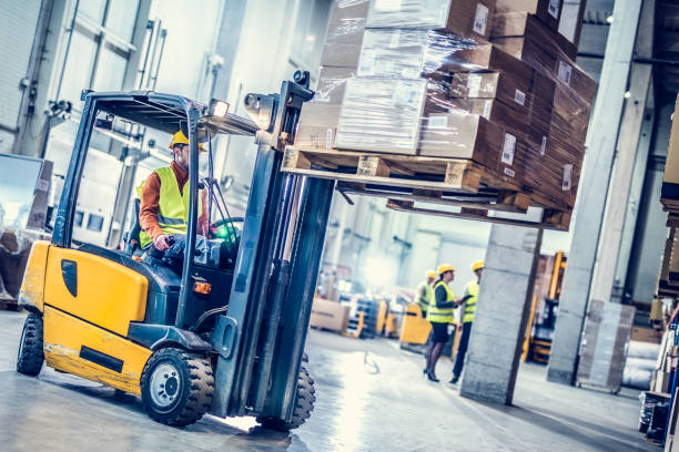 forklift moving stack of boxes - warehouse stock photos and pictures