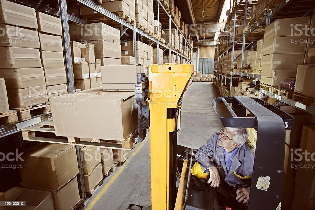 forklift operator at warehouse Loading, lifting cardboard boxes on pallet royalty-free stock photo