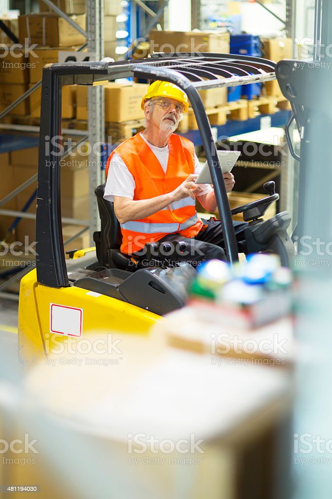 Forklift operator looking at a digital tablet stock photo