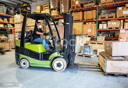 Forklift operator with protective mask at a Miami warehouse during 2020 pandemic