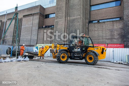 London, England - March 10, 2015: Construction site and a yellow JCB Forklift: Teleporter Telescopic Handler Loadall forklift. The driver is in the cab of the forklift moving a pallet. The Tate Modern is behind and people can be seen on the balcony