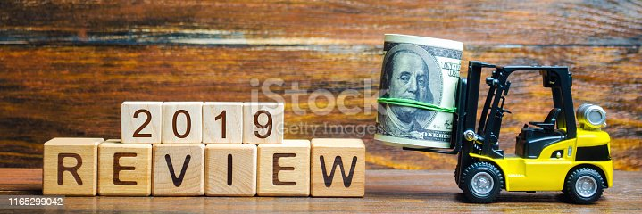 istock Forklift truck carries a bundle of dollars to inscription Review 2019. Audit of business and enterprises, government agencies and services. Annual report and financial performance indicators 1165299042