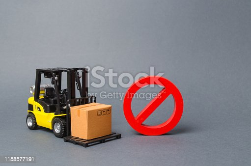 184640907 istock photo Forklift truck carries a cardboard box near a red symbol NO. Embargo, trade wars. No delivery. Restriction on the importation of goods, proprietary for business. Inability to sell products, ban import 1158577191