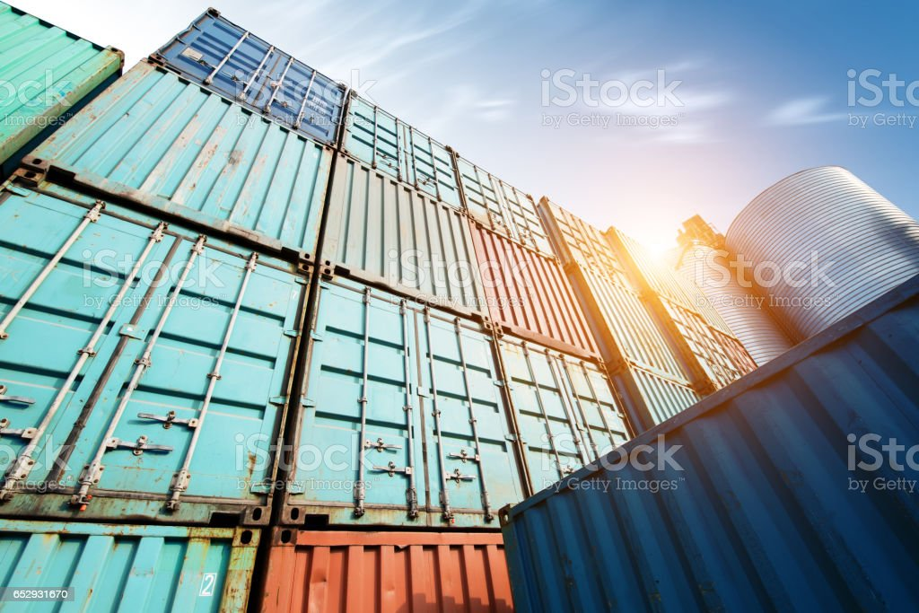 Forklift truck lifting cargo container in shipping yard or dock yard against sunrise sky with cargo container stack in background for transportation import,export and logistic industrial concept stock photo