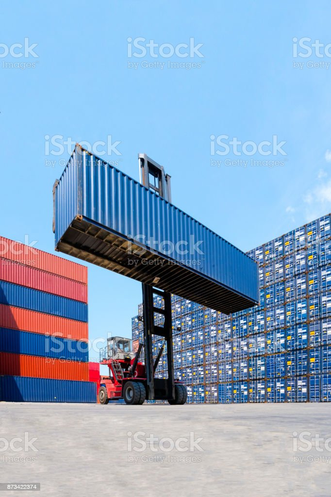 Forklift truck lifting cargo container in shipping yard or dock yard with cargo container stack in background stock photo