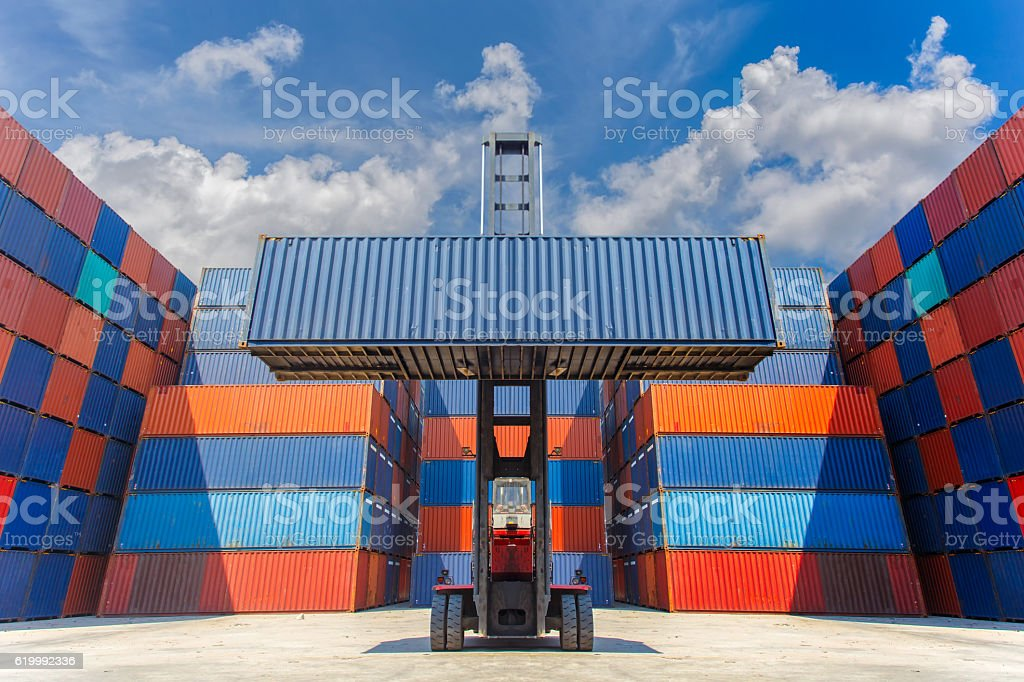 Forklift truck lifting cargo container in shipping yard stock photo