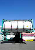 Forklift with driver loading a blank chemical container against clear sky.