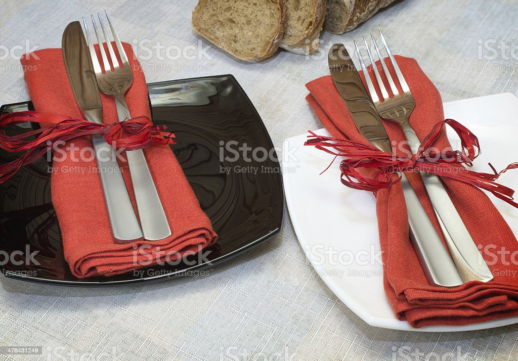 forks and knives with red napkin lying on plates royalty-free stock photo