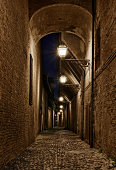 Forli, Emilia-Romagna, Italy: narrow dark alley in the old town - ancient Italian street at night with lampposts and cobbled pavement