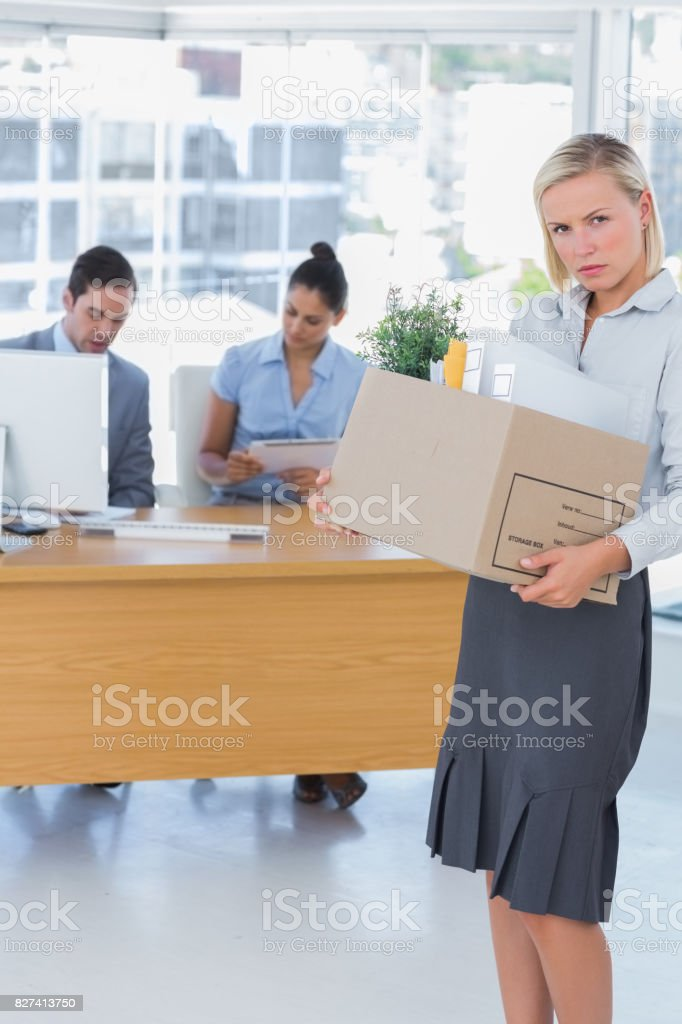 Forlorn businesswoman leaving office after being let go stock photo
