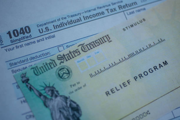 Form 1040 U.S. Individual Income tax return next to the Stimulus Check Relief program. Close up view. Form 1040 U.S. Individual Income tax return next to the Stimulus Check Relief program. Close up view. stimulus check stock pictures, royalty-free photos & images
