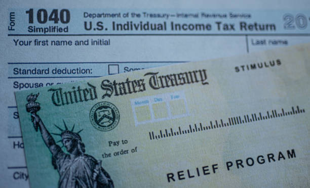 Form 1040 U.S. Individual Income tax return next to the Stimulus Check Relief program. Close up view. Washington, DC, USA - July, 8, 2020: Form 1040 U.S. Individual Income tax return next to the Stimulus Check Relief program. Close up view. stimulus check stock pictures, royalty-free photos & images