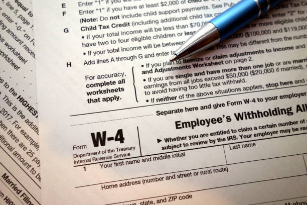 W-4 form and a pen stock photo