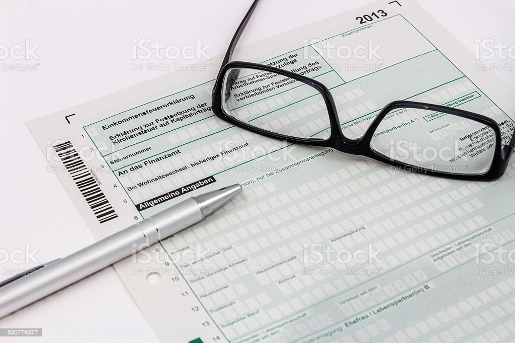 Form of income tax return with ball pen and glasses stock photo