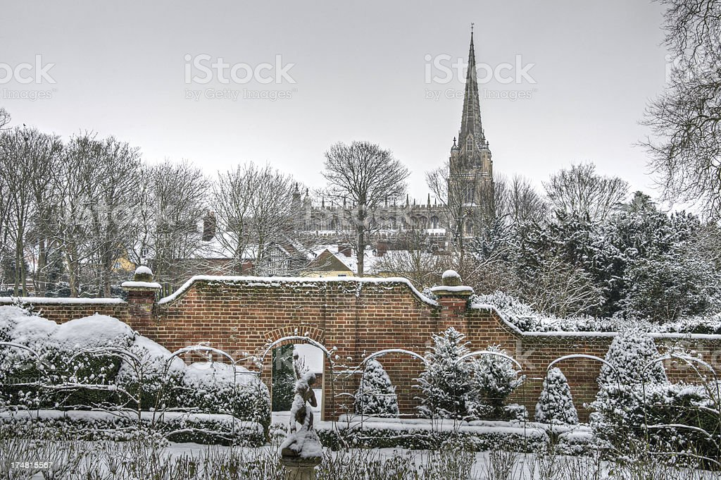 Formal garden covered in snow with wall and church royalty-free stock photo