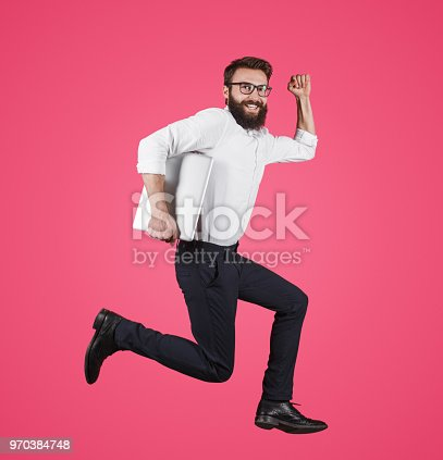 istock Formal man with laptop running on pink 970384748