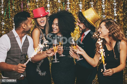 Multi-Ethnic group of cheerful people in formal wear holding chanpagne glasses and sparklers on a celebration.