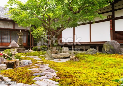 Formal rock and moss garden at Japanese Buddhist temple with a large Japanese maple growing at the end of a footpath.