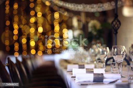 Formal wedding place setting on long table background focus on wine glass