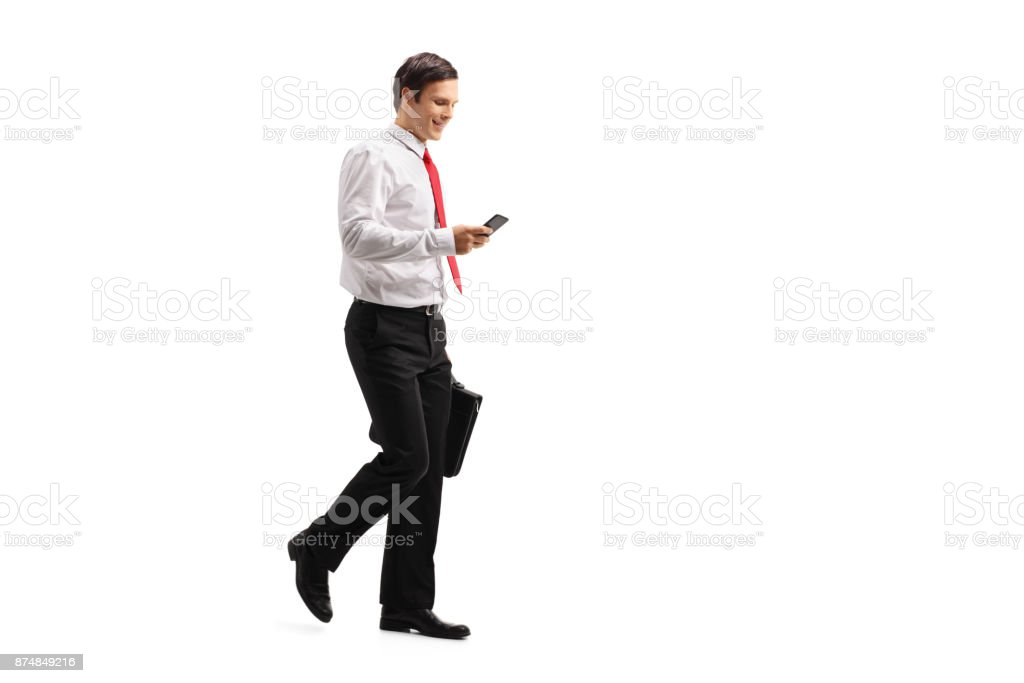 Formally dressed guy with a briefcase using a phone and walking stock photo