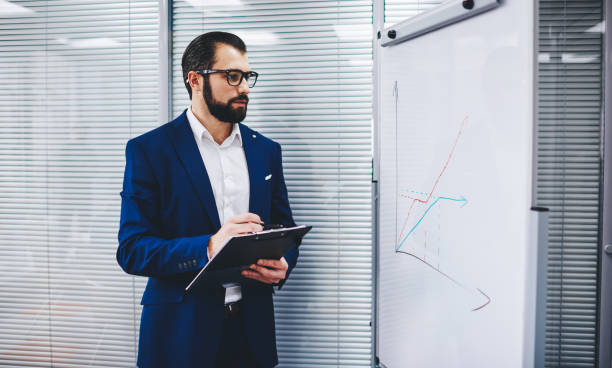Formally dressed male entrepreneur in optical spectacles for vision correction analyzing statistic infographic from office flipchart, experienced businessman checking revenue marketing diagram stock photo