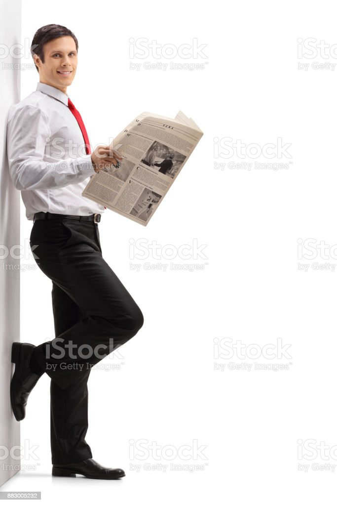 Formally Dressed Man With A Newspaper Leaning Against A Wall Stock