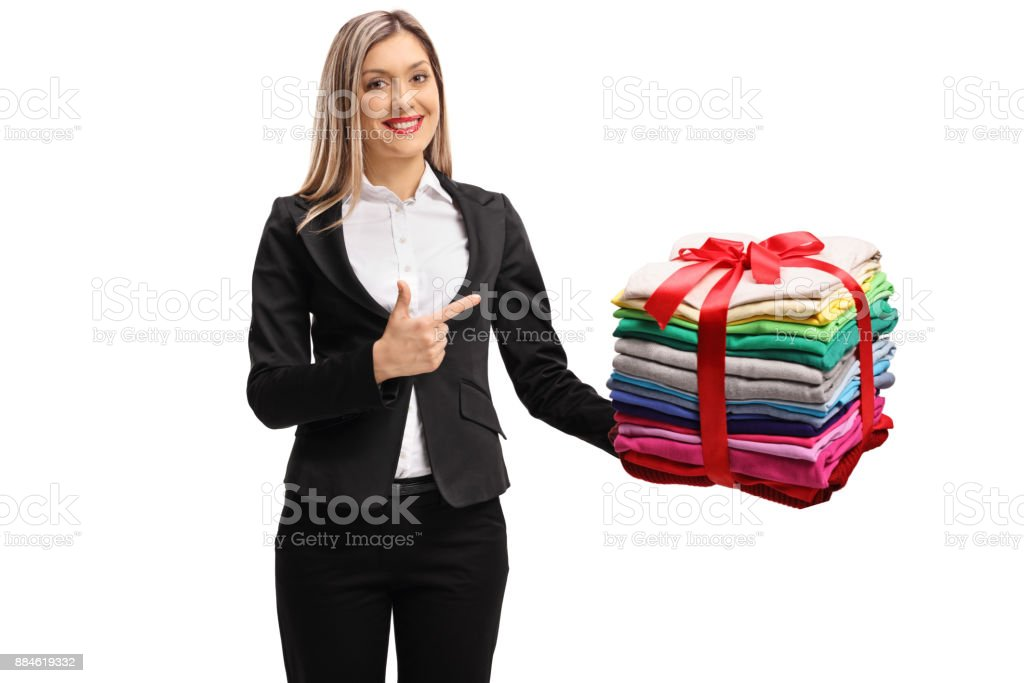 Formally Dressed Woman Holding A Stack Of Packed And Ironed Clothes