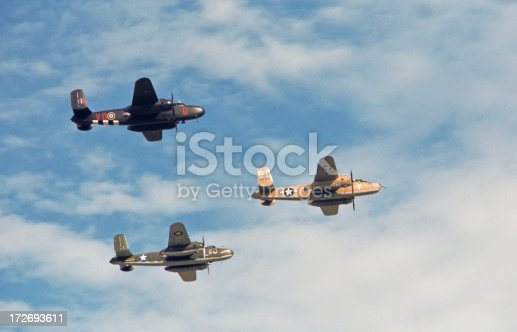 A formation of three B-25 Mitchell medium bombers flies by overhead.  All aircraft appear as they would have have during World War II.  The left most aircraft is painted in the colors of the British Royal Air Force.