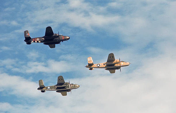 Formation of Three World War II B-25 Bombers A formation of three B-25 Mitchell medium bombers flies by overhead.  All aircraft appear as they would have have during World War II.  The left most aircraft is painted in the colors of the British Royal Air Force. bomber plane stock pictures, royalty-free photos & images