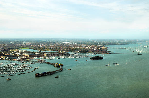 Former Royal Navy buildings in Gosport View over Gosport and part of Portsmouth Harbour, seen from the Spinnaker Tower. Many old military buildings are evident as well as new developments and marinas. Two old warships are 'laid up in ordinary' to the right of the scene, indicative of how the area is changing form military to civilian. (Some reflections, distortion and effects of curved and tinted window glass. Shot on a cloudy day with watery sunlight beginning to appear.) naval base stock pictures, royalty-free photos & images