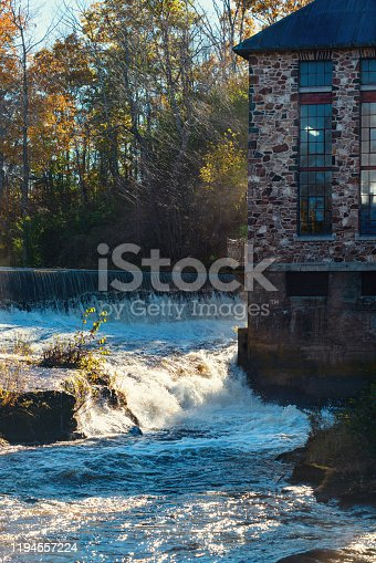 Water flows over a dam at the site of a former sawmill.