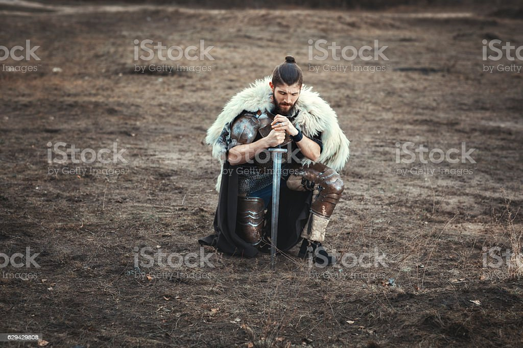 Formidable man with a sword in field sad. stock photo