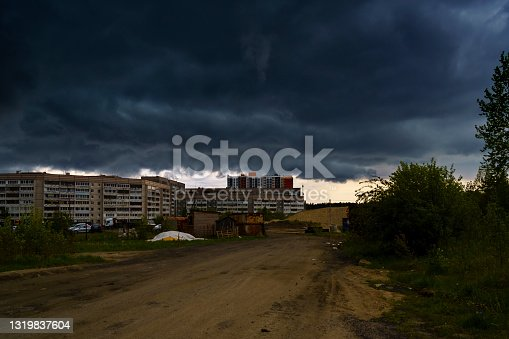 Formidable storm clouds enveloped the outskirts of the city in darkness in the spring before a heavy downpour with lightning and thunder