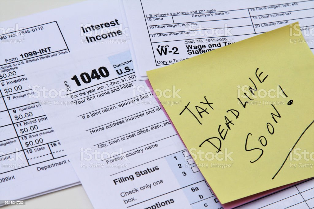 IRS forms with note pad saying Tax Deadline Soon stock photo