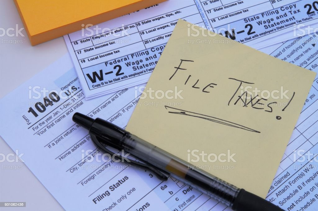 IRS forms with sticky note saying File Taxes stock photo