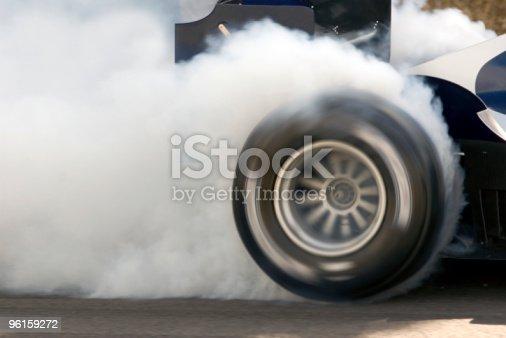 2006 Formula One Grand Prix car smoking its super slick tires.  The Formula One Grand Prix car is engulfed in white smoke.