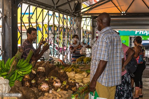 Fort-de-France, Martinique - December 19, 2016: Local man picks goods on the picturesque fruit and vegetable covered market of Fort de France, the capital of Martinique, an overseas department of France.