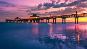A colorful golden and purple sunset falls beneath the horizon at the Fort Myers Beach Pier in Florida, USA. Long exposure seascape background with copy space.