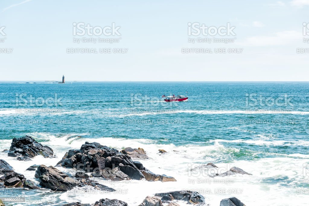 Fort Williams park in Cape, Elizabeth Maine during summer day with red tour boat by Ram Island stock photo