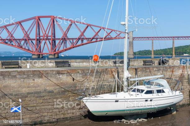 Forth Bridge, railway bridge over Firth of Forth near harbor with sailboat in Queensferry, Scotland